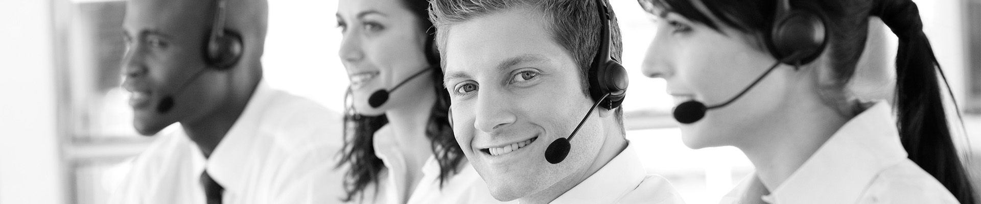 young make smiling whilst working in a call centre